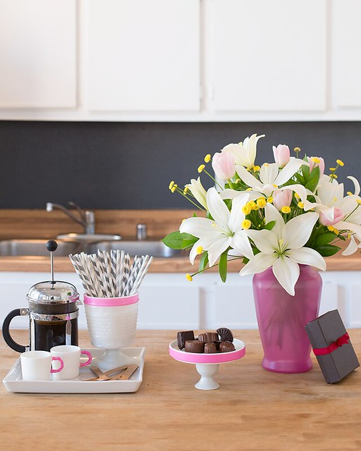 coffee chocolate candy in box with ribbon white Asiatic lilies in a purple glass vase ceramic cups and straws on counter in kitchen