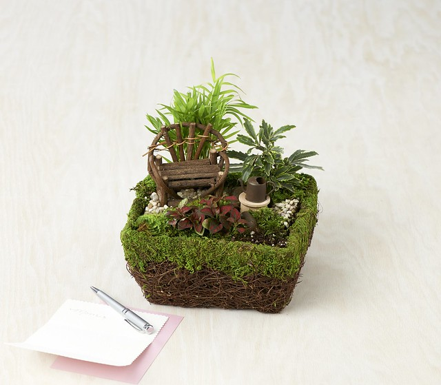 little zen garden in a basket with miniature wood chair watering can potted plants and a note with silver pen