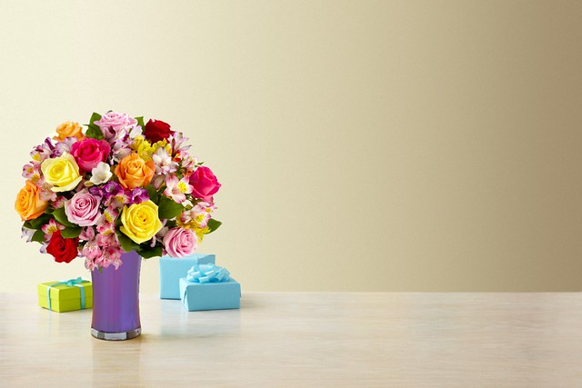 Smiles and Sunshine Bouquet with alstroemeria Peruvian lilies and multi-colored roses in a purple glass trumpet vase on a white table with wrapped gifts