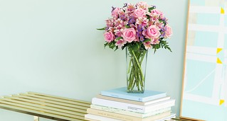 pink roses and alstroemeria Peruvian lilies lavender button poms in a glass vase atop stacked books on a shelf and a blue wall and framed art by ProFlowers | by ProFlowers.com