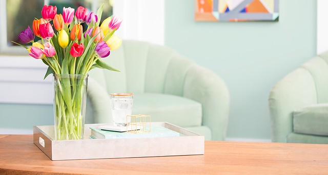 assorted multi-color tulips in a pink tray box with glass and books and light blue chair