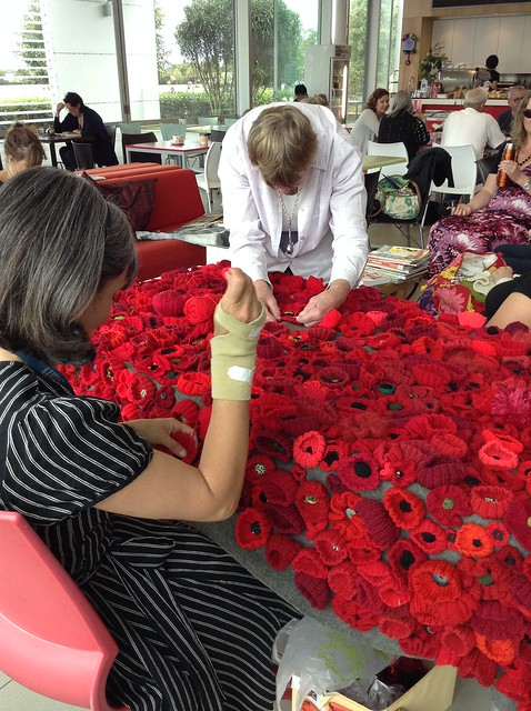 Sewing the poppies onto the blanket - Christchurch City Libraries