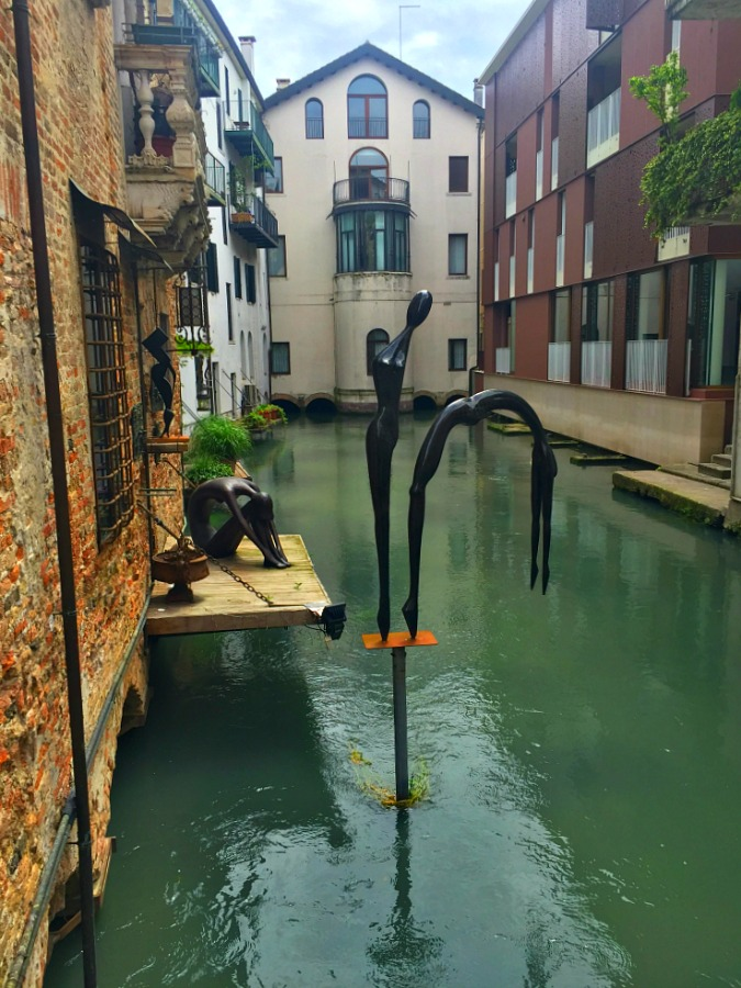 Statues taking a dip in one of Treviso Italy's canals