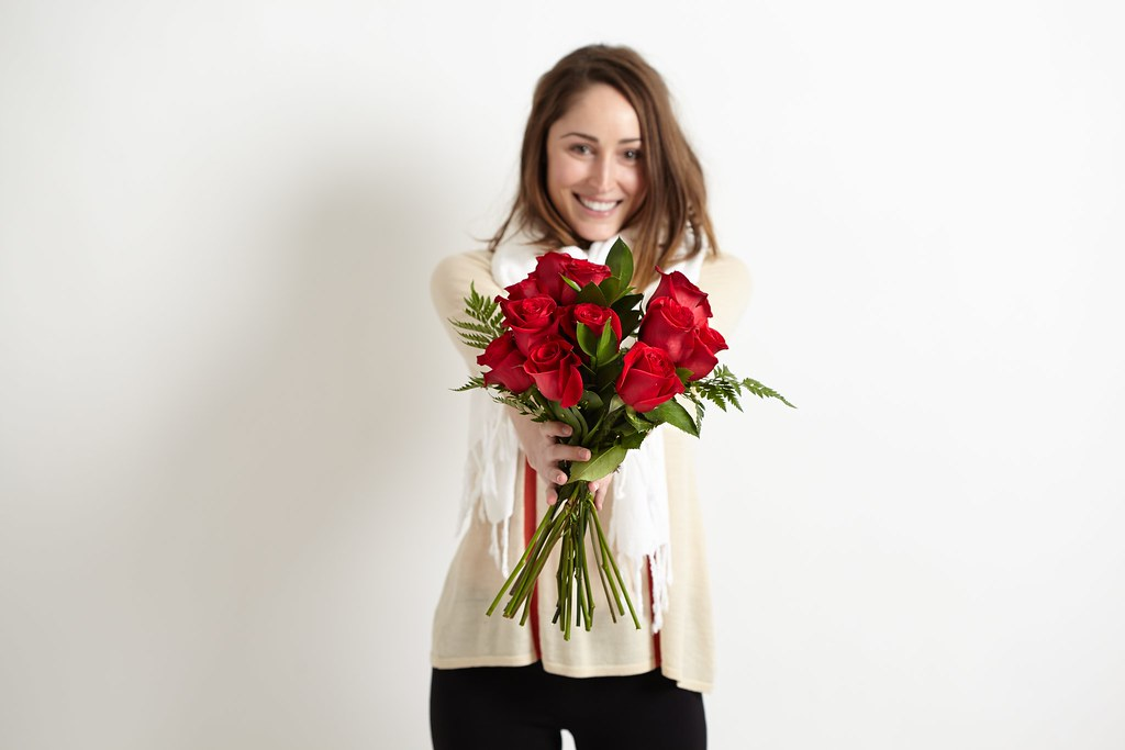 woman in white sweater and black pants with bouquet of red roses