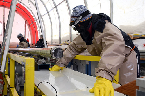 A science team member prepares to extract an ice core from the drill | by U.S. Ice Drilling