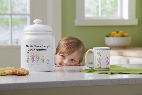 little kid peeking over a counter at a personalized cookie jar on kitchen counter with personalized mug from Personal Creations and fruit bowl in background | by PersonalCreations.com