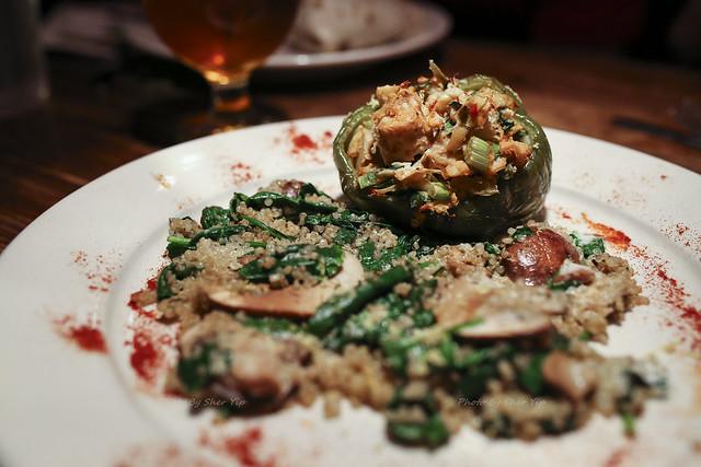 Tempeh, artichoke & spring onion stuffed bell pepper served over herbed mushroom & spinach quinoa with a lemon & caper coconut sauce - Morgantown Brewing Company
