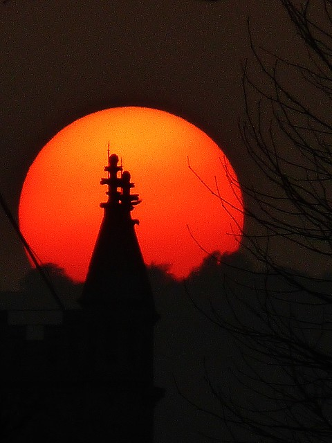 Silhouette of church spire against setting sun