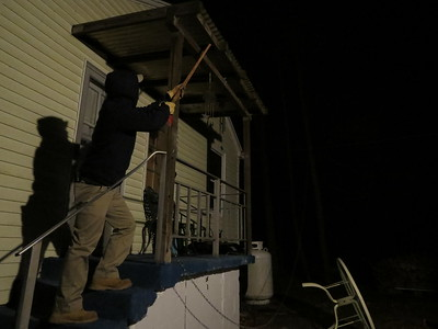 man in long pants, hooded sweatshirt and gloves holding pole up to porch overhang at night.
