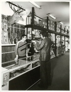 A customer looking at a shotgun at a sports shop in Wellington, (Mel Lewis Sports), Lambton Quay | by Archives New Zealand