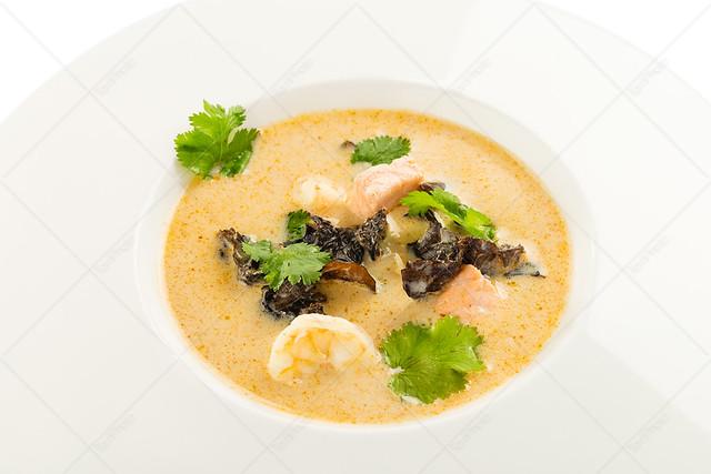 Thai coconut milk soup Tom Kha with salmon, shrimp and mushrooms
