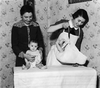 Nurse weighing a baby using a weighing hook / Une infirmière pèse un bébé à l'aide d'un crochet-peseur