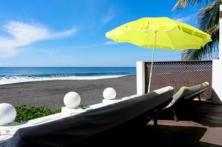 Sunbeds and green umbrella beside the beach | by wuestenigel