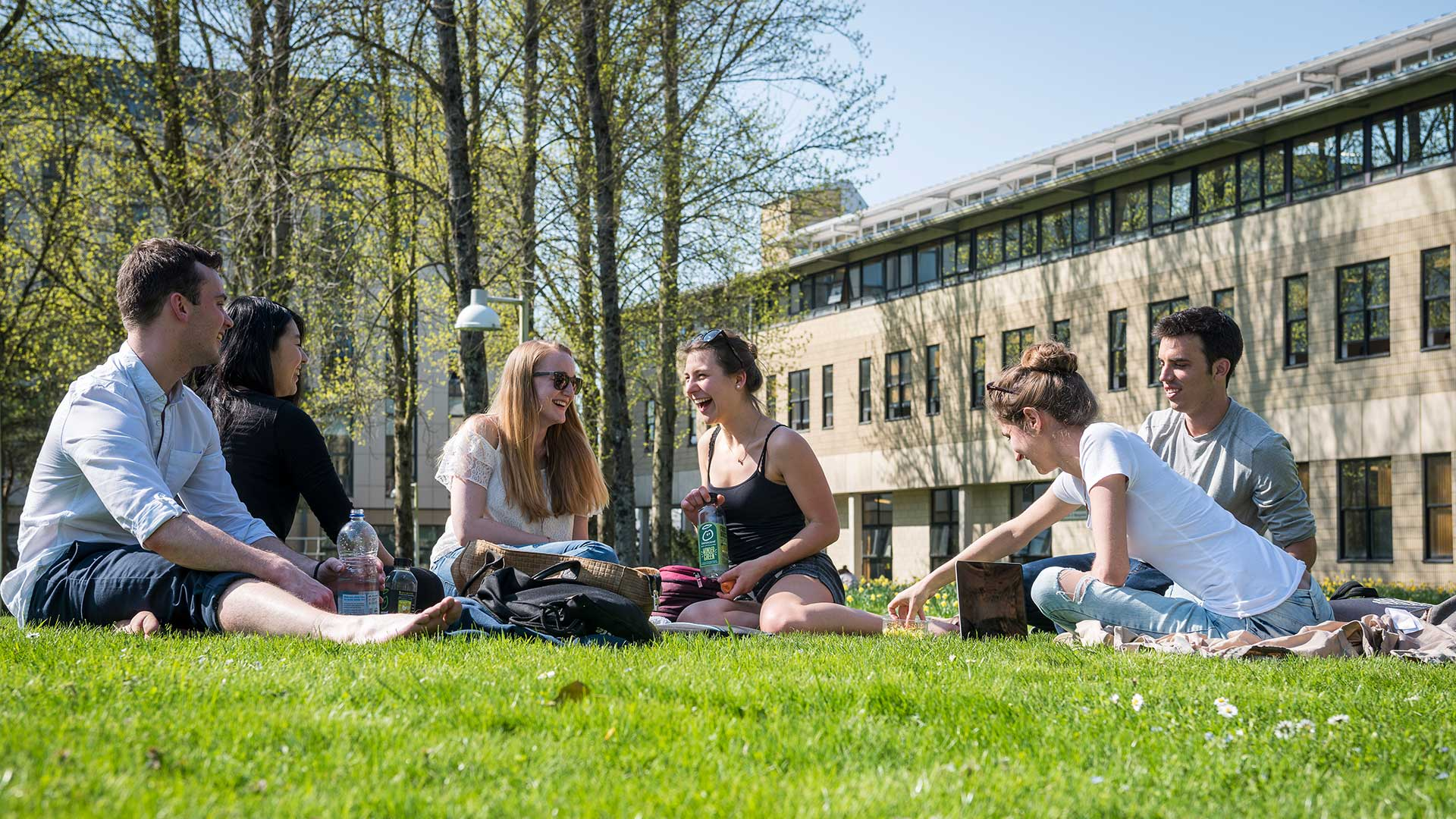 A group of six people chat in the sun on campus