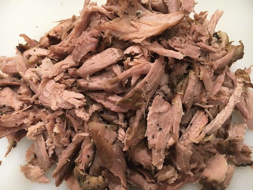 pulled pork butt from masterbuilt electric smoker with dry rub spices on white cutting board | by yourbestdigs