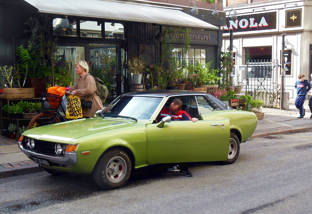 Copenhagen Girl on bike #15  shops by bike while man uses his 1973 Toyota Celica DT33400 in Copenhagen