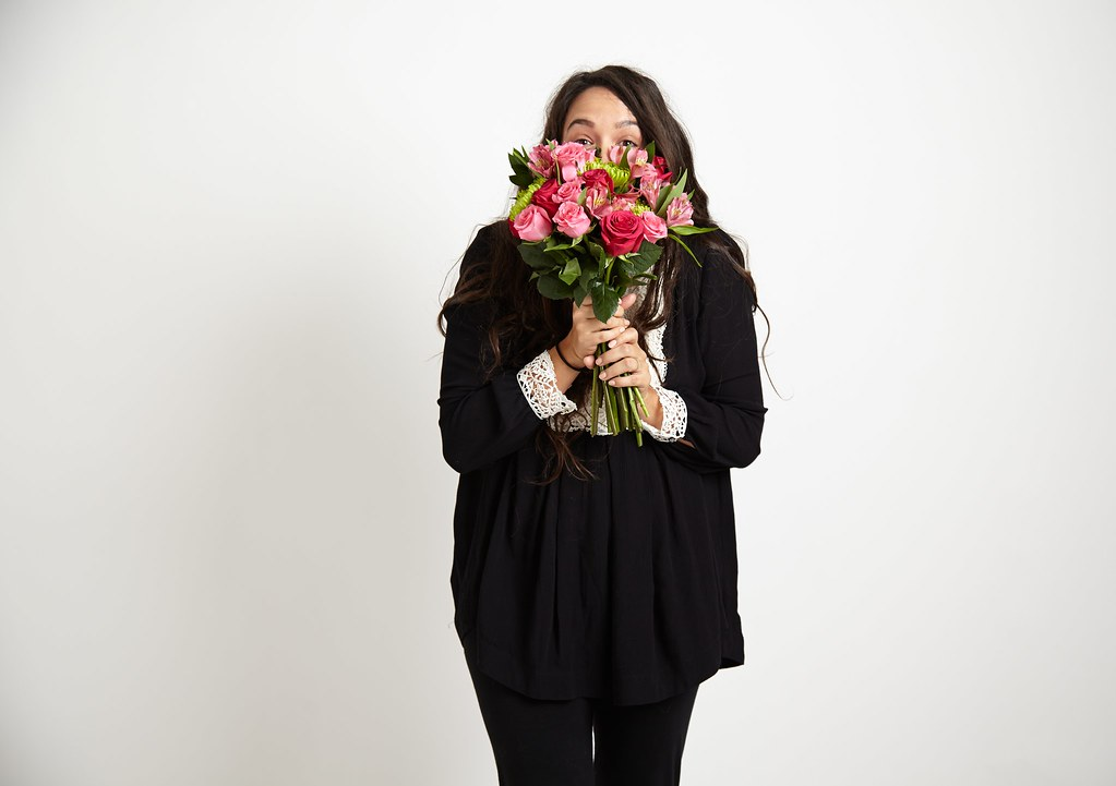 woman in black with bouquet of red and pink roses alstroemeria Peruvian lilies and green mums