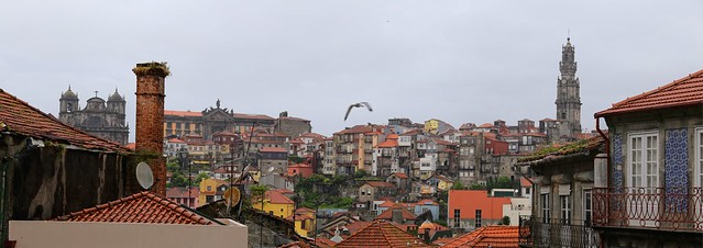 Terracotta roofs and the old bell tower rises high above rainy Porto