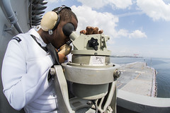 Quartermaster Seaman Ruben Jeanpierre uses an alidade and sound-powered telephone as USS George Washington (CVN 73) departs Yokosuka, May 18. (U.S. Navy/MC2 Paolo Bayas)