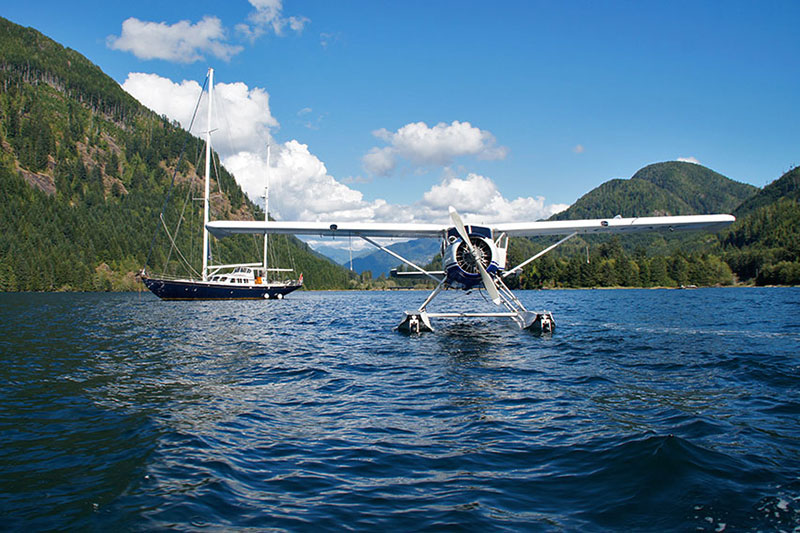 Floatplane delivers passangers to a luxury yacht in Fair Harbour, Kyuquot Sound, Vancouver Island, British Columbia, Canada. Photo: Santa Brussouw.