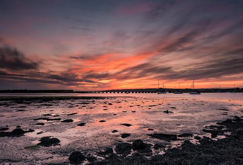 sunset fireinthesky langstoneharbour haylingislandhampshiresouthcoastukmudseaweedyachtsboatscloudsreflectionsfilterleendgradnikond8002470mmapril2015sunsetsnapper