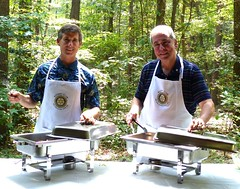 PDG Matt Kane & Club President Scott Tarkenton prepare to dish-out picnic lunch to all present.