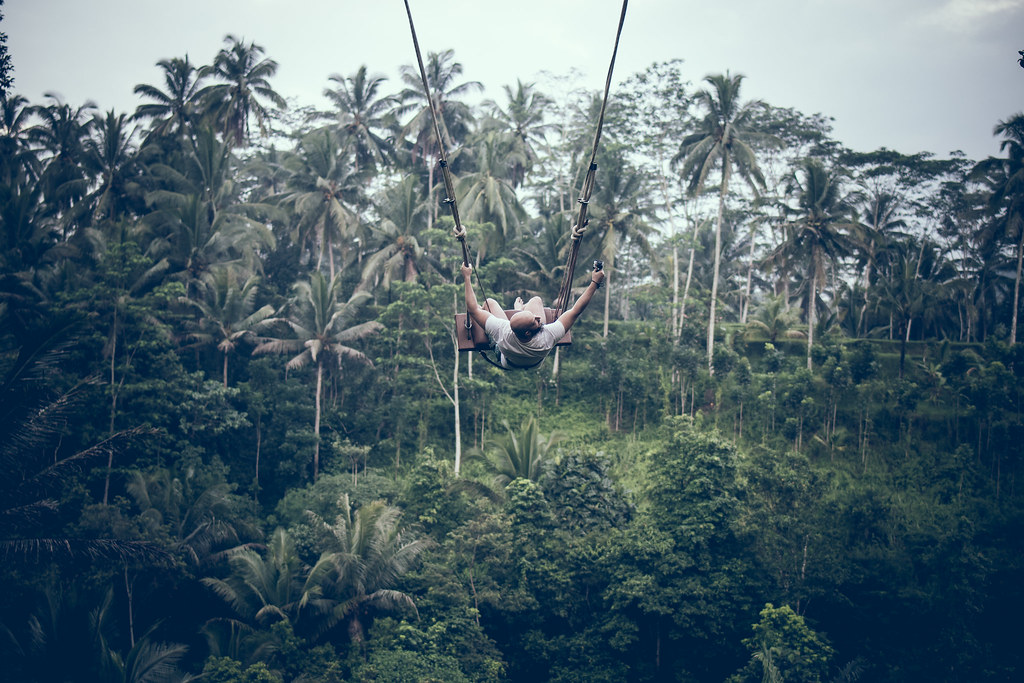 BALI, INDONESIA - DECEMBER 26, 2017: Man having fun on the swing with action camera in the jungle of Bali island, Indonesia. Rainforest, swing.