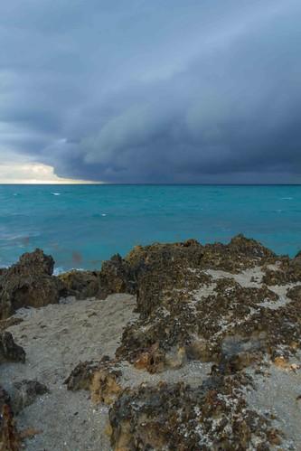 storm clouds rain ocean dark sand beach rock blue