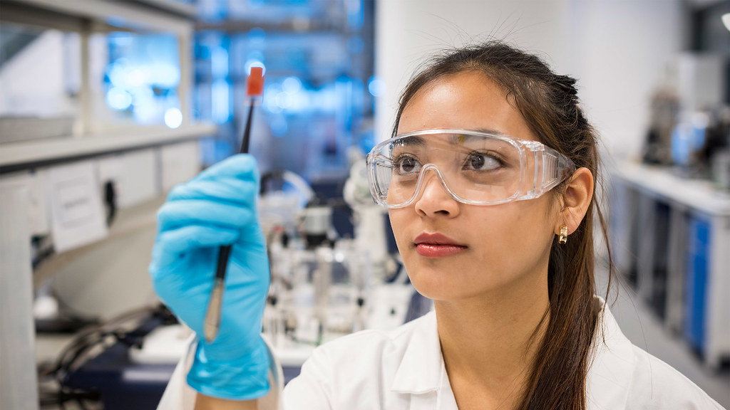 A chemical engineering student examines her project in a chemical engineering lab.