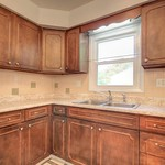 Nice counter space in the kitchen with tile backsplash. Cabinets have modern polished nickel hardware.
