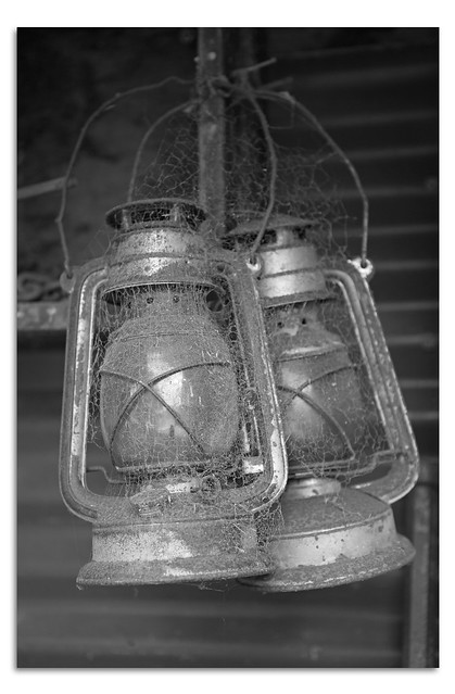 Black & White of two hurricane oil lamps in a barn