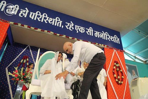 Satguru Mata Savinder Hardev Ji puts the white scarf (Dupatta), around Rev. Sudiksha Ji's neck through a devotee.