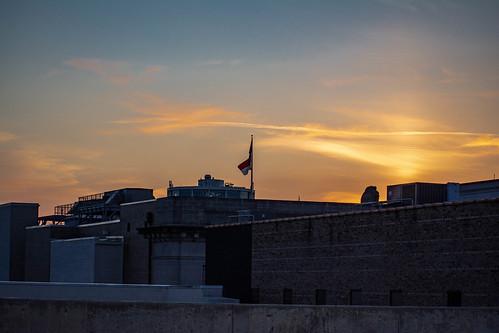 sun sunset sky clouds flag buildings downtown architecture color orange yellow blue city