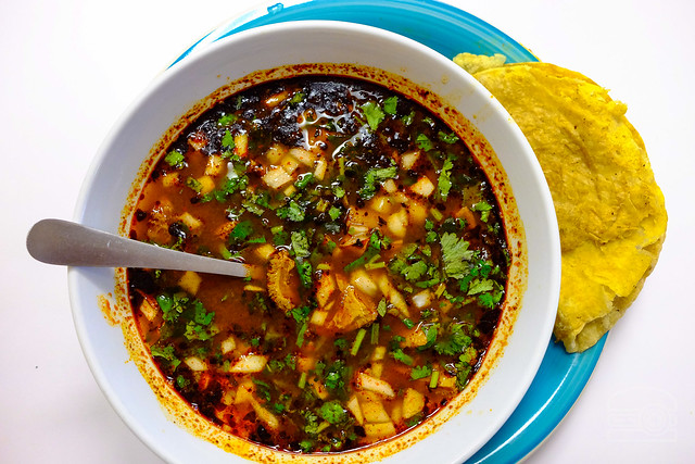 Menudo, or pancita is a traditional Mexican soup, made with beef stomach in broth with a red chili pepper base. Hominy, lime, onions, and oregano are used to season the broth -  La Tapatia Market and Tacos