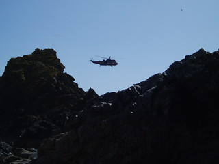 Rescue helicopter and seagull over the rocks at Kynance Cove, The Lizard, Cornwall