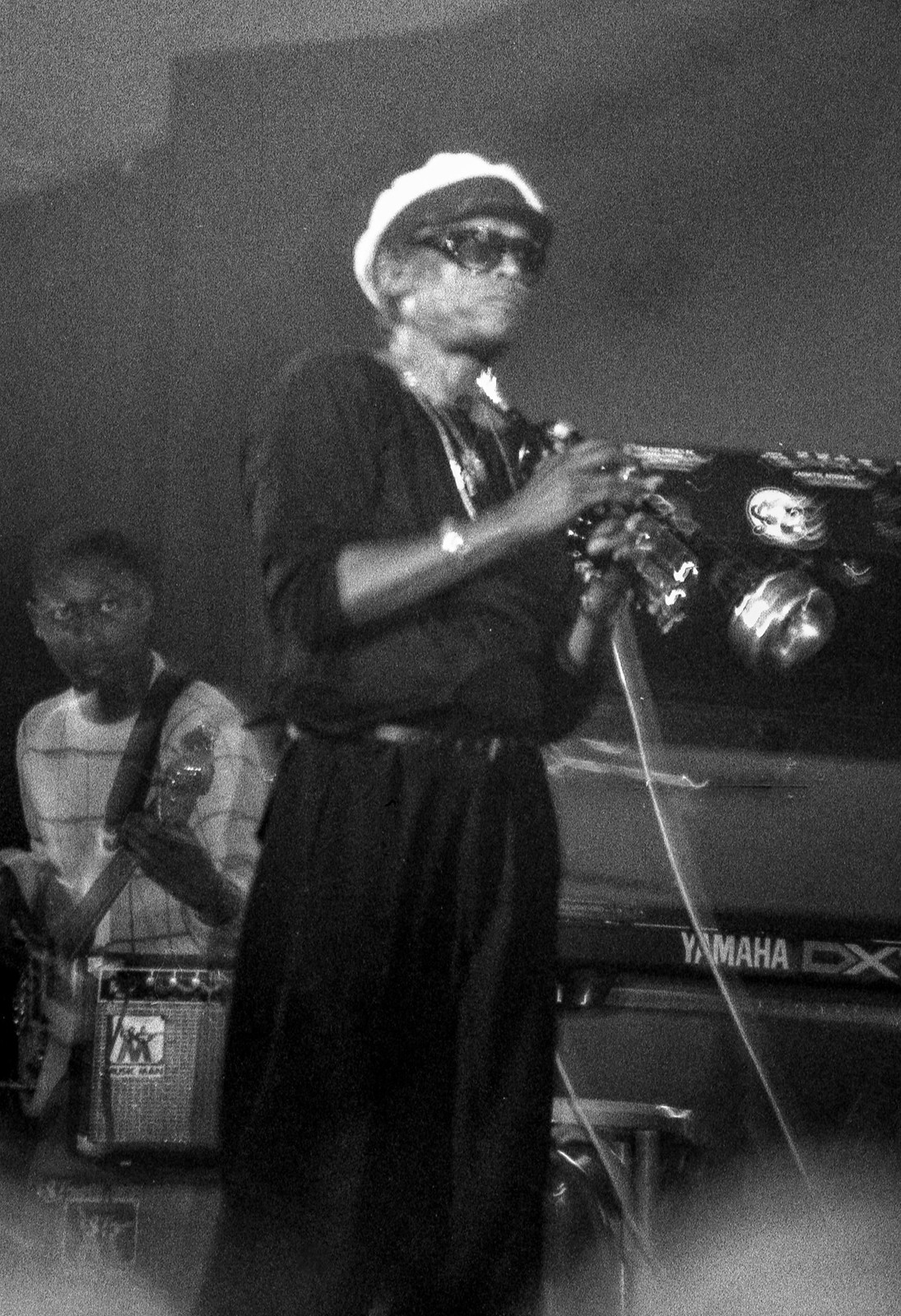 A black and white photo of Miles Davis standing on a stage holding a trumpet with Darryl Jones behind him holding a guitar