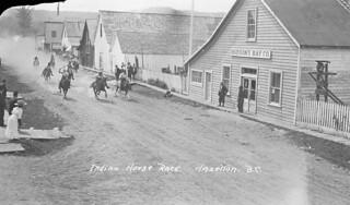 First Nations men racing horses past the Hudson's Bay Company store, Hazelton, British Columbia / Course de chevaux entre membres des Premières Nations devant le magasin de la Compagnie de la Baie d'Hudson, Hazelton (Colombie-Britannique)