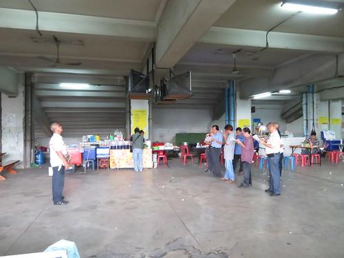 タイの競馬場内にある屋台の脇で予想する人々