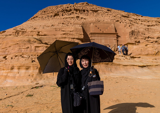 Japanese tourists in front of a nabataean tomb in madain saleh archaeologic site, Al Madinah Province, Al-Ula, Saudi Arabia