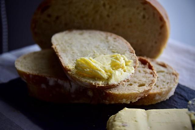 Manteiga caseira temperada de leve com pimenta do reino, páprica, alho e ervas. Para acompanhar e espalhar todo esse sabor, um pão caseiro fermentado por 5 horas e depois assado enchendo a casa com aquele cheiro gostoso de pão.