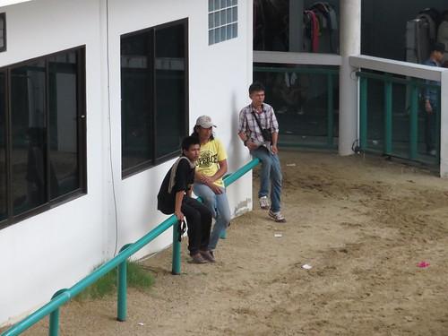 ロイヤルターフクラブ競馬場の装鞍所でたむろする人々