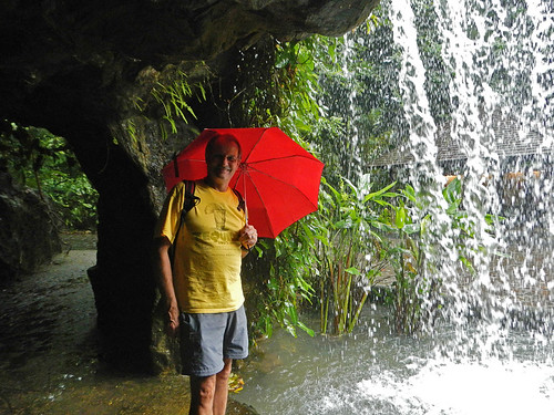 Standing under a waterfall with a red umbrella in Singapore Botanical Garden