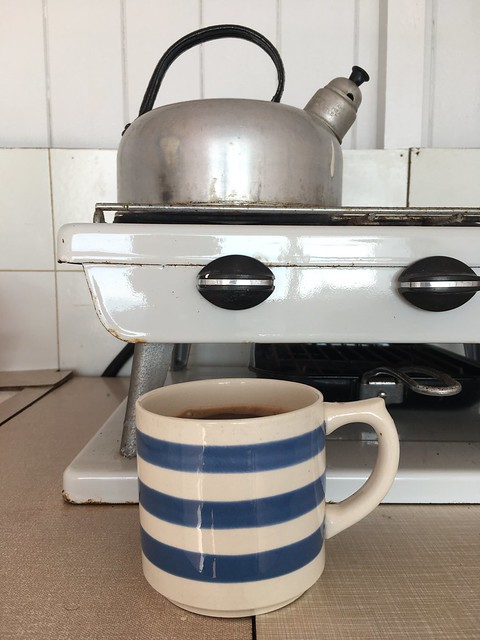 A photo of a blue-and-white striped cornishware mug in front of a kettle on a gas hob