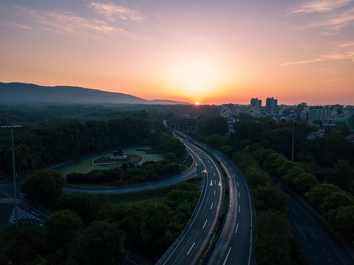 sunrise highway landscape city cityscape mountain transportation square nature plant tree vehicle sky cloud outdoor drone aerial spring